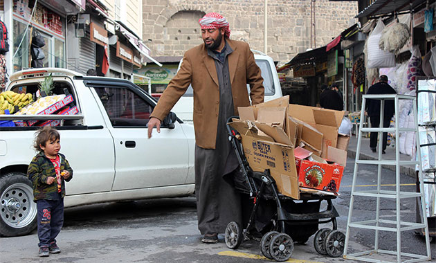 Oğlunun bebek arabasıyla atık topluyor